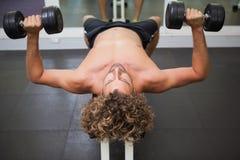 Bez koszuli mężczyzna ćwiczy z dumbbells w gym Zdjęcie Stock