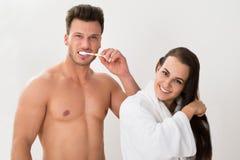 Bez koszuli mężczyzna szczotkuje jego zęby i jej żona zgrzywionego włosy Obraz Royalty Free