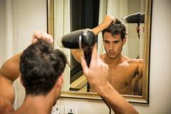 Bez koszuli młodego człowieka suszarniczy włosy z hairdryer Obraz Stock