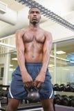 Bez koszuli mięśniowego mężczyzna czajnika podnośny dzwon w gym Zdjęcie Royalty Free