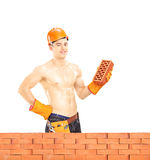 Bez koszuli mięśniowy męski pracownik budowlany trzyma cegłę Obrazy Royalty Free
