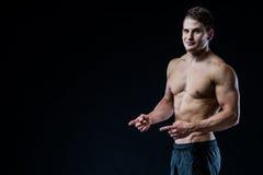 Bez koszuli mięśniowy sportowy mężczyzna punkt z dwa palcami i rękami pusty copyspace Seksowny bodybuilder pokazuje jego ciało Obrazy Royalty Free