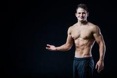 Bez koszuli mięśniowy sportowy mężczyzna punkt z jeden ręką pusty copyspace Seksowny bodybuilder pokazuje jego ciało na czerni Zdjęcia Royalty Free