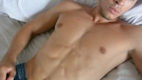 Bez koszuli seksowny samiec model kłama samotnie na jego łóżku zdjęcie wideo