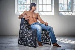 Bez koszuli sprawności fizycznej samiec model w cajgi siedzi na krześle Zdjęcia Royalty Free