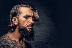 Bez koszuli, tatuująca brodata samiec nad zmrok winiety popielatym backgro, Fotografia Royalty Free