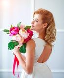 Bezaubern der gl?cklichen und frohen Braut der jungen Frau im wei?en Kleid mit Blumenstrau? von Blumen im Studio lizenzfreies stockbild