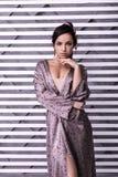 Bezaubern des leuchtend schönen weiblichen Posierens über gestreiftem Hintergrund stockbilder
