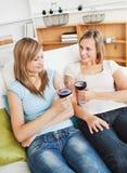 Bezaubern von zwei Frauen, die den Wein sitzt auf einem Sofa trinken lizenzfreie stockfotografie