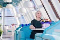 Bezaubernde alte Frau, die in einem Restaurant oder in einem Café, heller Innenraum sitzt stockbild