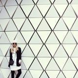 Bezaubernde blonde Stellung an der Wand städtische Modeart Lizenzfreie Stockfotografie