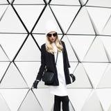 Bezaubernde blonde Stellung an der Wand Städtisches Modeschwarzes und w Lizenzfreie Stockbilder