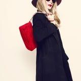 Bezaubernde Blondine im klassischen schwarzen Mantel und im roten Hut Herbst fashi stockfoto