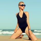 Bezaubernde Blondine im modernen Badeanzug auf dem Strand stockbild