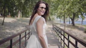 Bezaubernde brunette tragende Sonnenbrille des jungen Mädchens des Porträts und langes weißes Sommermodekleid, die entlang hölzer stock video footage
