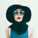 Bezaubernde Dame im Weinlesehut und Sonnenbrille neigt Modehafen Lizenzfreies Stockfoto