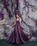 Bezaubernde Fee von Blumen und von Floraständen nahe Steinwand wirft playfully für die Kamera in langem magischem elegantem auf stockbilder