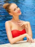Bezaubernde Frau, die im Pool aufwirft Stockbild