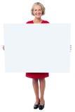 Bezaubernde Frau, die leeres Anzeigenbrett hält Stockfotos