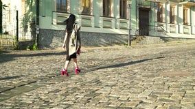 Bezaubernde Frau mit rosa Tasche und in den modischen Schuhen gehend an der Steinstraße in der Stadt stock video footage