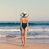 Bezaubernde gebräunte Dame im modernen Badeanzug und im Hut auf dem bea Lizenzfreie Stockbilder
