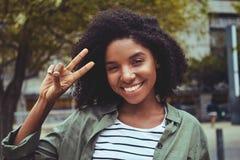 Bezaubernde junge Frau, die Friedensgeste macht stockbild