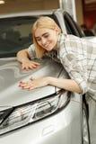 Bezaubernde junge Frau, die neues Automobil kauft stockfoto