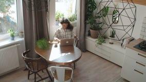Bezaubernde junge Frau, die zu Hause auf Laptop-Computer schreibt stock video footage