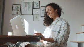 Bezaubernde junge Frau, die zu Hause auf Laptop-Computer schreibt stock video