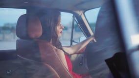 Bezaubernde junge Frau ist in einem Auto, das traurig auf einem Beifahrersitz, hintere Ansicht schaut stock video footage
