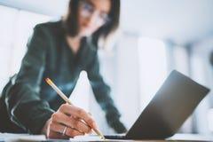 Bezaubernde junge Geschäftsfrau, die etwas in Notizblock beim Arbeiten im Büro schreibt Unscharfer Hintergrund lizenzfreie stockbilder