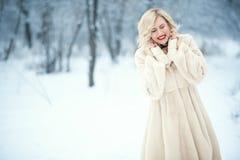 Bezaubernde lachende blonde Dame mit perfektem bilden tragende luxuriöse weiße Schwingenpelzmantelstellung auf schneebedecktem Hi lizenzfreies stockbild