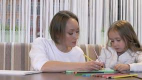 Bezaubernde Mutter der jungen Frau zeichnet mit ihrer netten kleinen Tochter stock footage