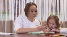 Bezaubernde Mutter der jungen Frau zeichnet mit ihrer netten kleinen Tochter stock video