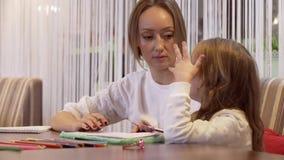 Bezaubernde Mutter der jungen Frau zeichnet mit ihrer netten kleinen Tochter stock video footage