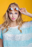 Bezaubernde schöne blonde Frau in der Sonnenbrille und im blauen Hemd auf gelbem Hintergrund Glückliche Sommerzeit Lizenzfreie Stockfotografie