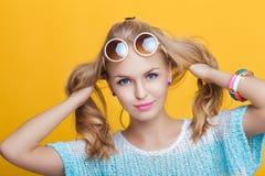 Bezaubernde schöne blonde Frau in der Sonnenbrille und im blauen Hemd auf gelbem Hintergrund Glückliche Sommerzeit Stockfotos