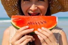 Bezaubernde schöne junge Frau, die Wassermelone isst, um ihren Durst in der Sommersaison am Strand unten abzukühlen und zu lösche lizenzfreies stockfoto