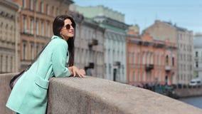 Bezaubernde stilvolle touristische Frau, die historische Stadt vom Damm hat positives Gefühl bewundert stock video