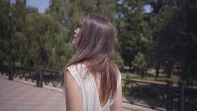 Bezaubernde tragende Sonnenbrille des jungen Mädchens des Porträts und langes weißes ein Sommermodekleid, das draußen geht Freize stock footage