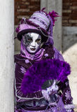 Bezaubernder Frauenausführender mit purpurrotem Kostüm und venetianische Maske während Venedig-Karnevals Stockbild