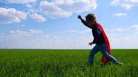 Bezaubernder Junge, der auf dem grünen Gras läuft Ein Kind in einem roten Mantel stellt den Flug des Supermannes dar stock video footage