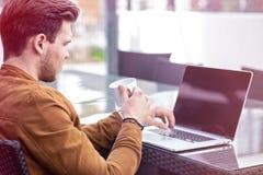 Bezaubernder junger erwachsener Mann, der an Laptop auf Morgen-Zeit im Freien arbeitet lizenzfreie stockfotografie