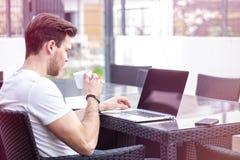 Bezaubernder junger erwachsener Mann, der an Laptop auf Morgen-Zeit im Freien arbeitet lizenzfreie stockfotos