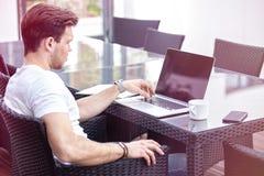 Bezaubernder junger erwachsener Mann, der an Laptop auf Morgen-Zeit im Freien arbeitet stockbilder