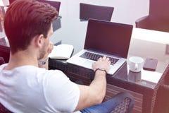 Bezaubernder junger erwachsener Mann, der an Laptop auf Morgen-Zeit im Freien arbeitet lizenzfreie stockbilder