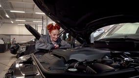 Bezaubernder weiblicher Automechaniker, der zur Kamera, arbeitend an der Garage lächelt stock video