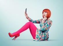Bezauberndes junges Mädchen, das mit einem intelligenten Telefon auf Hintergrund sitzt lizenzfreie stockfotografie