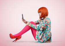 Bezauberndes junges Mädchen, das mit einem intelligenten Telefon sitzt stockfotos