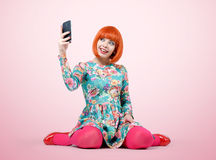 Bezauberndes junges Mädchen, das mit einem intelligenten Telefon sitzt stockfotografie